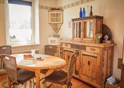 Zimmer mit Tisch, Stühlen und Kommode der Ferienwohnung Stephanides in Lemgo